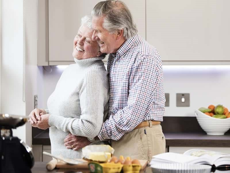 Older couple laughing in the kitchen of a Brio home
